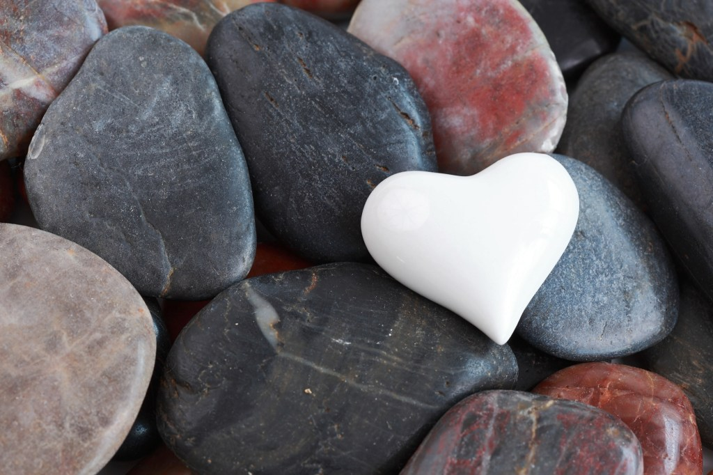 White heart shaped rock on bed of other black rocks