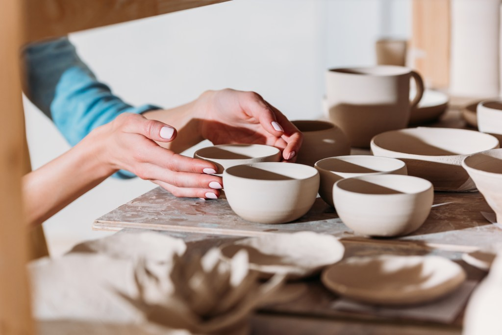 A potter putting the finishing touches on her ceramic bowls before firing