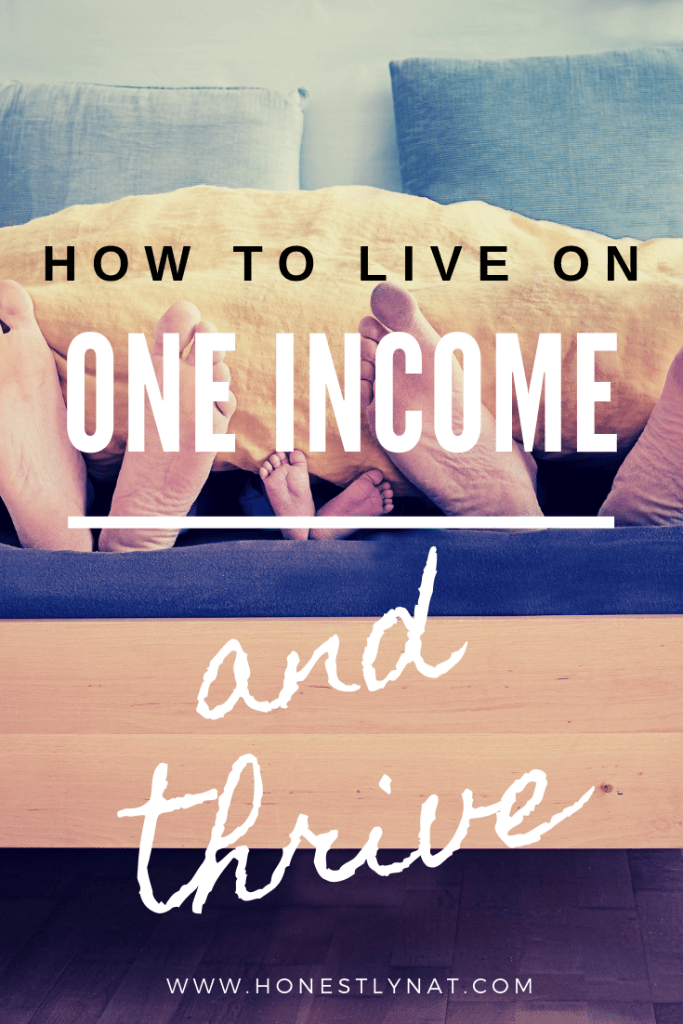 "Three sets of feet - Mom, Dad and toddler's - poking out at end of bed with the text overlay ""How to Live on One Income and Thrive"""