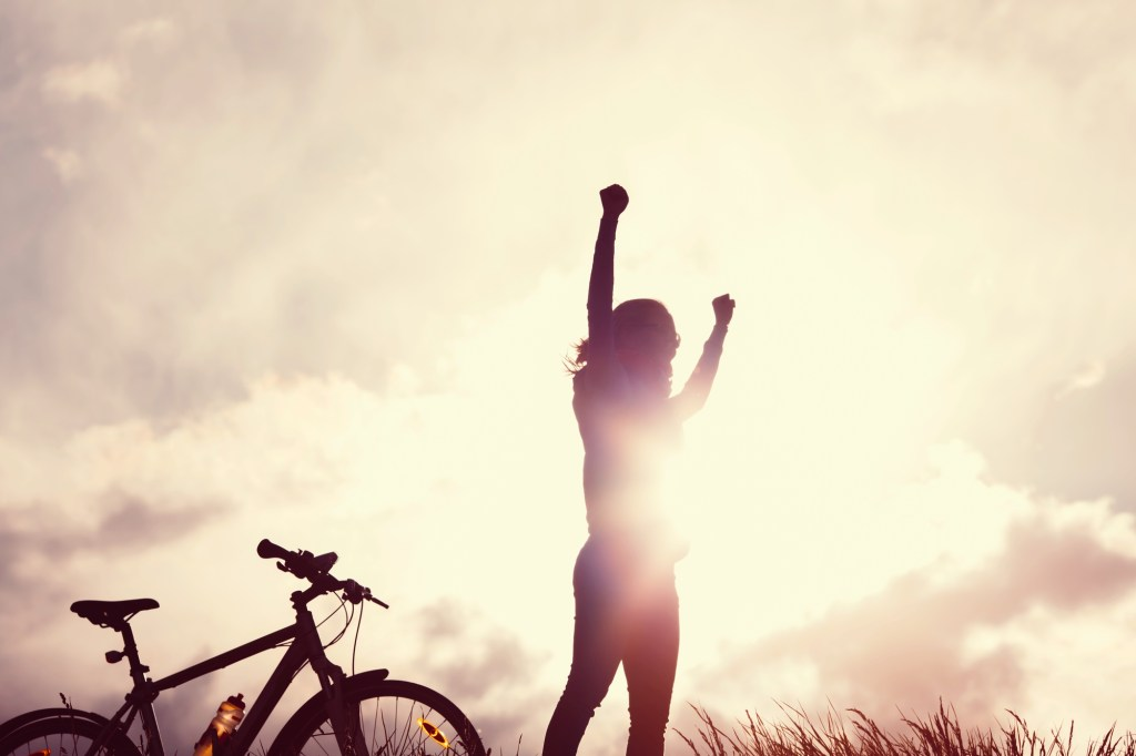 Female cyclist reaching her goal and celebrating