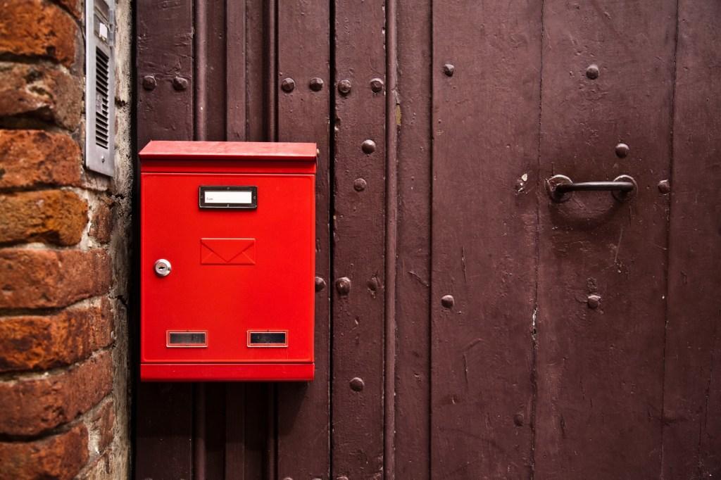 Red mailbox on brown door
