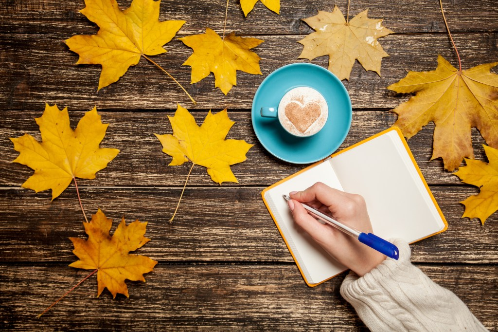 Woman writing in notebook on rustic background with cup of coffee