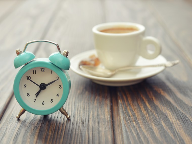 Vintage alarm clock with coffee cup on wooden surface