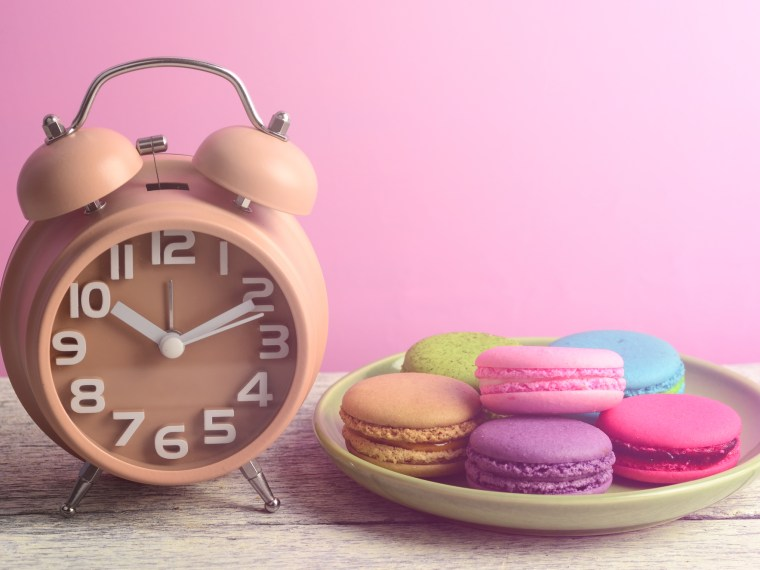 Clock on pink background with plate of macarons
