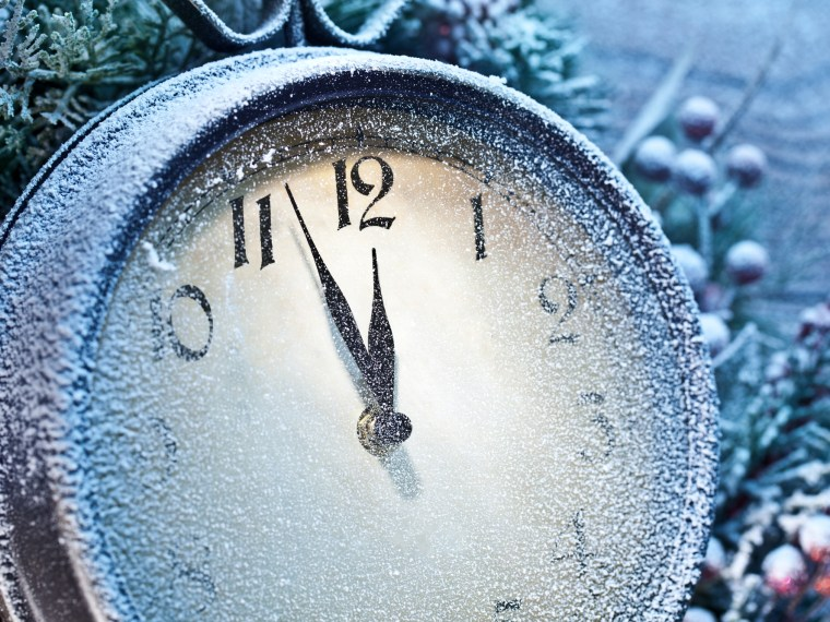 Clock covered in snow and awaiting the New Year