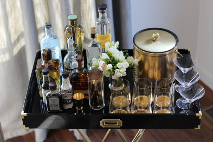 Bar Cart Essentials Black Tray Gold Handle Gold Ice Bucket Flower Arrangement Six Glasses Three Martini Glasses Liquor