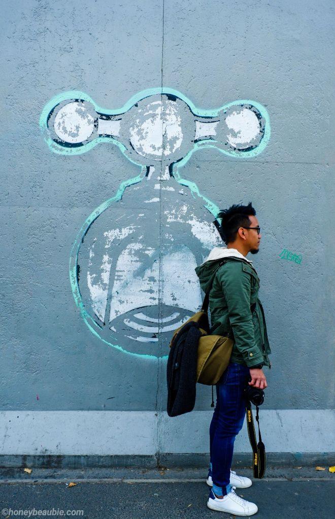 Man-standing-in-front-of-Berlin-Wall-mural-war-art