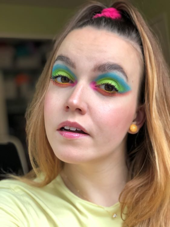 Emily is wearing a bright colorful eyeshadow look in blue, green, orange, and pink, created with the BH Cosmetics Take Me Back to Brazil Eyeshadow palette.