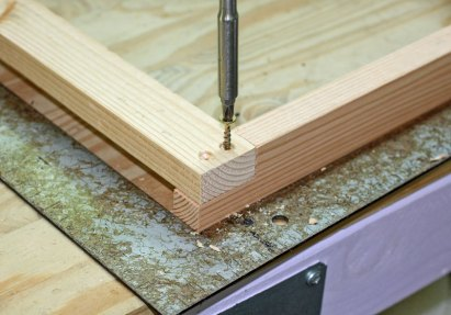 The holes were pre-drilled with a countersink. I used two screws per corner.