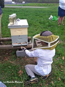 Here's our son Koty sitting with his new hive of bees last year.