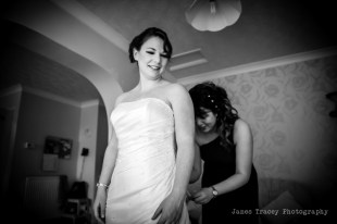 Honeyblossom Bridal boutique owner helps bride into wedding gown