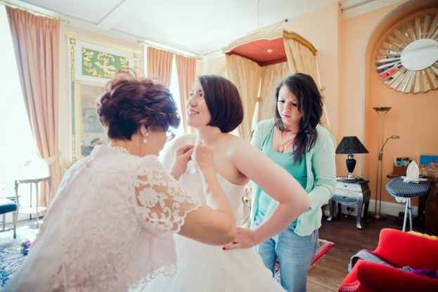 Honeyblossom Bridal owner helps bride into bridal gown