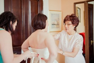 Honeyblossom Bridal owner Jenny helps bride into bridal gown