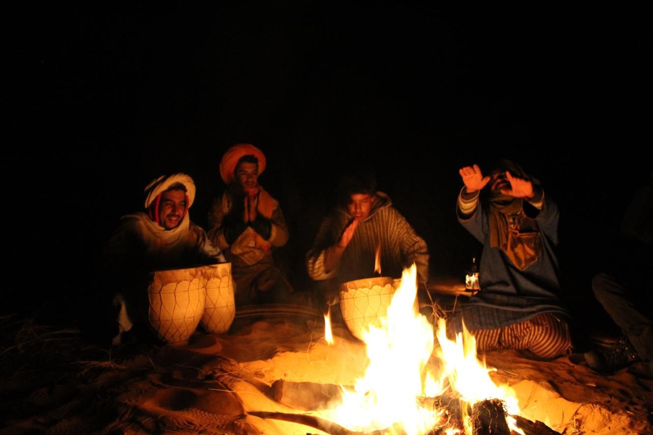 I Berberi cantano e suonano intorno al falò nel deserto del Sahara