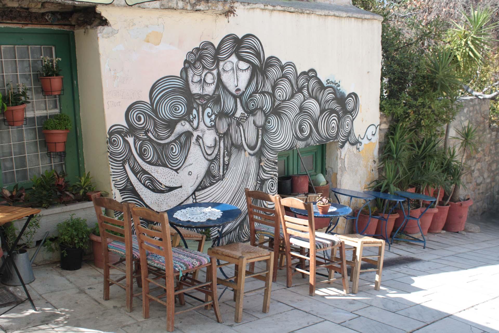 Street art à Athènes avec deux amants et petit restaurant