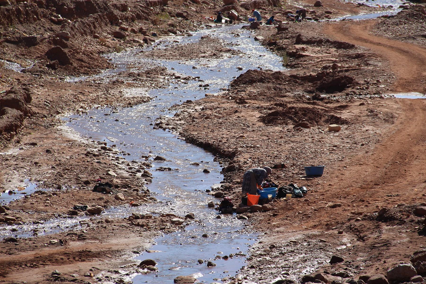 Donna che lava vestiti nel fiume nell'Alto Atlante