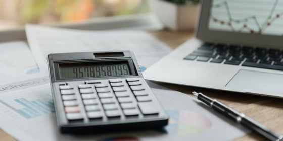 Laptop, calculator, pen, and paper reports representing accounting for small business.