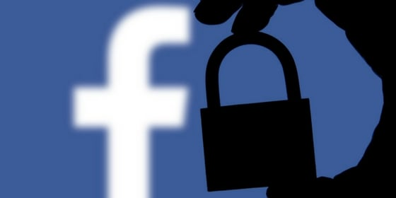 Hand holding padlock over Facebook logo representing historic pay wall updates in past Facebook algorithm changes.