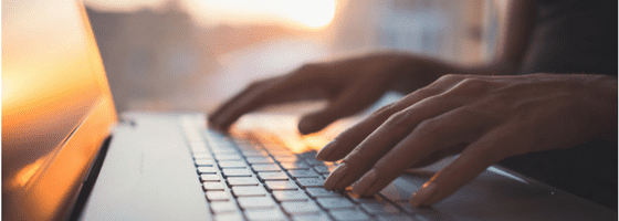 Woman copywriting on laptop in sunlight