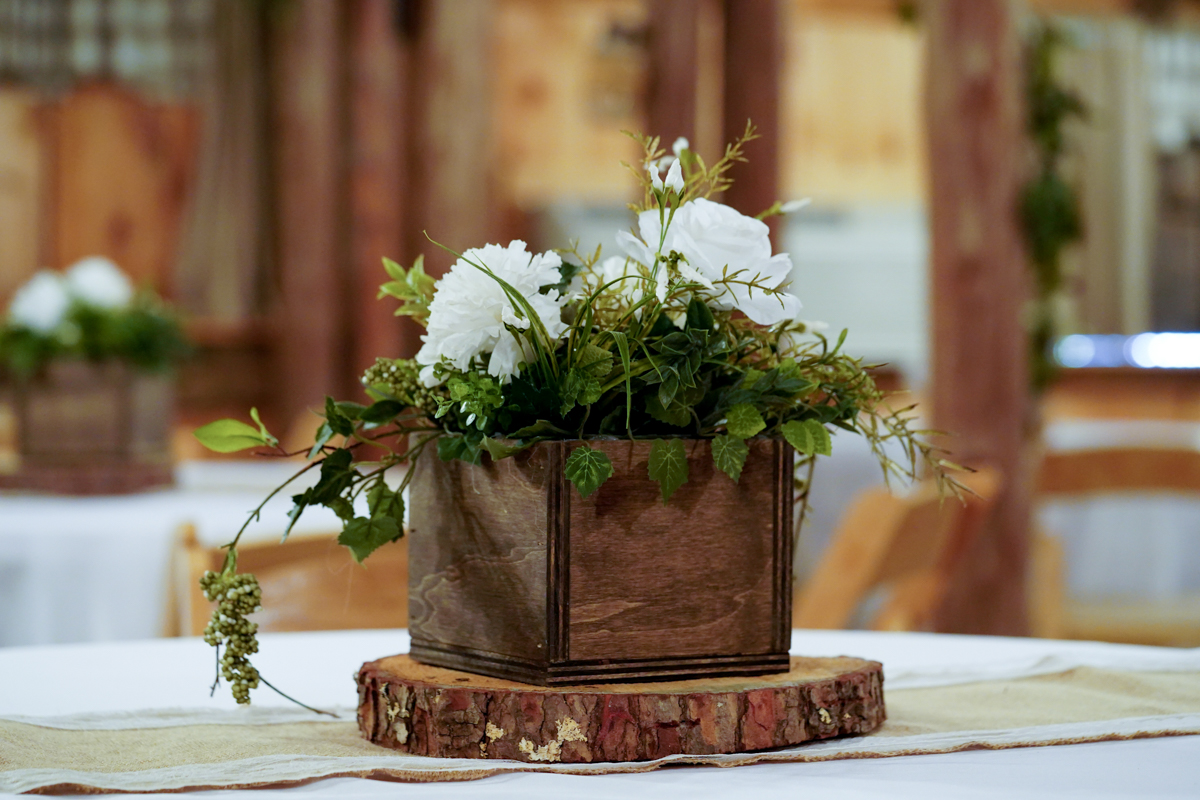 Hand made wooden centerpiece with greenery and white roses sitting on a log slice on top of a reception table