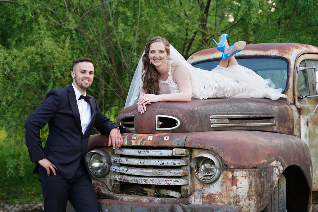 Bride laying on the hood of a 1950 Ford truck with blue high heels while her husband leans in toward her