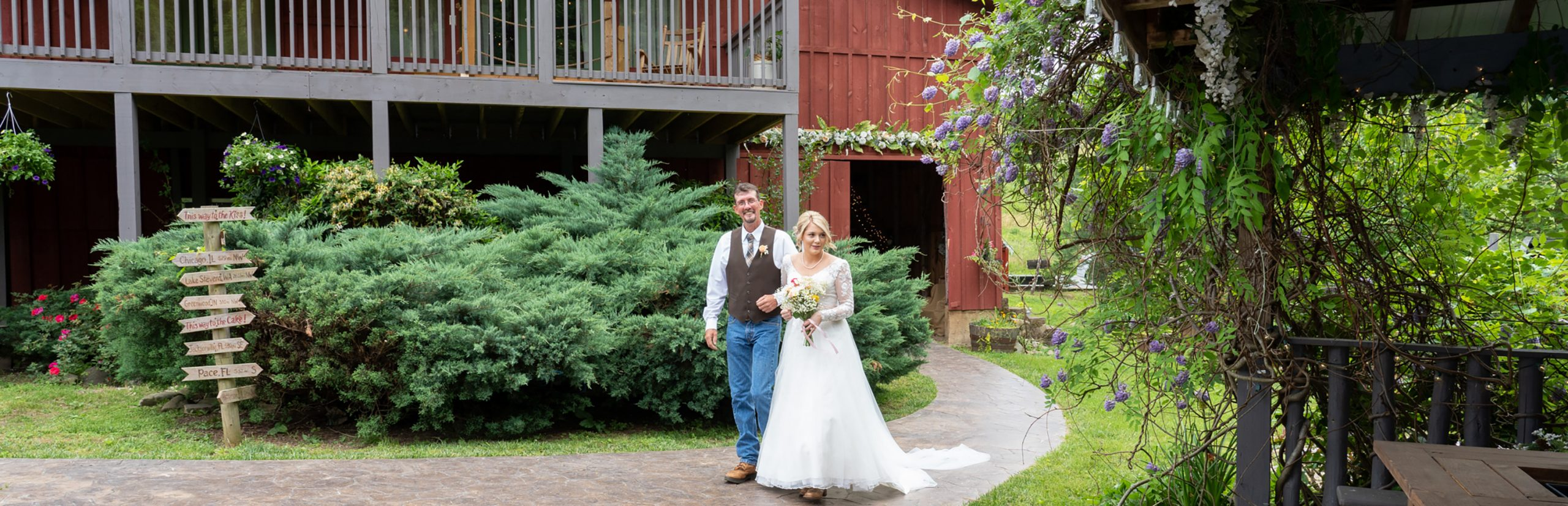 Father giving away his daughter down a garden path by a red barn at Honeysuckle Hills wedding venue