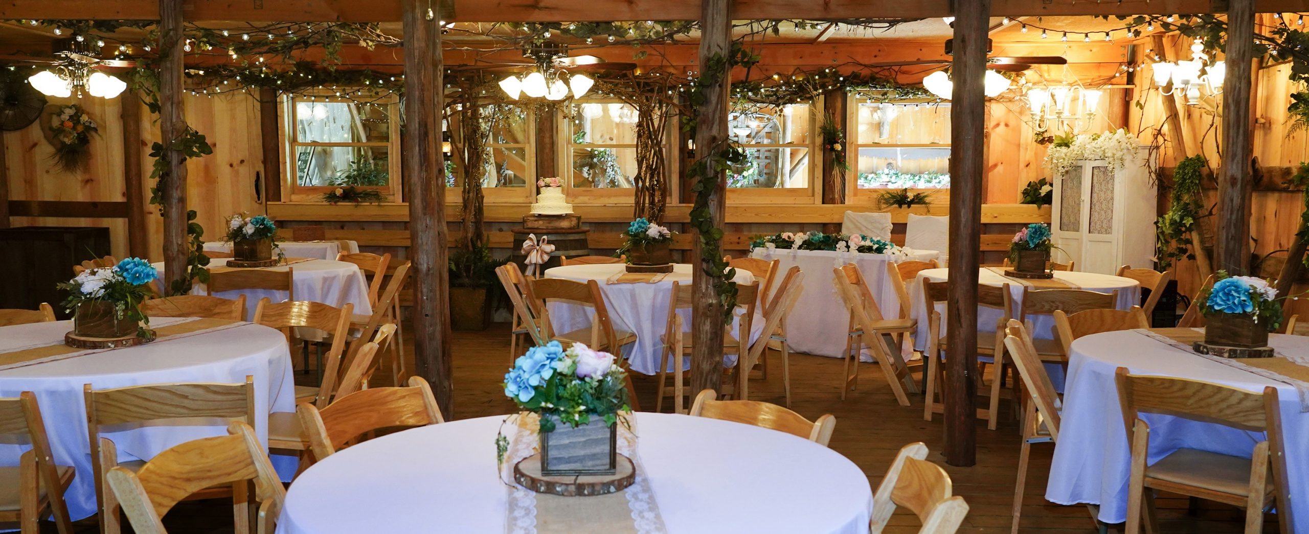 Honeysuckle Hills reception hall with round tables and log slice centerpieces on white linens