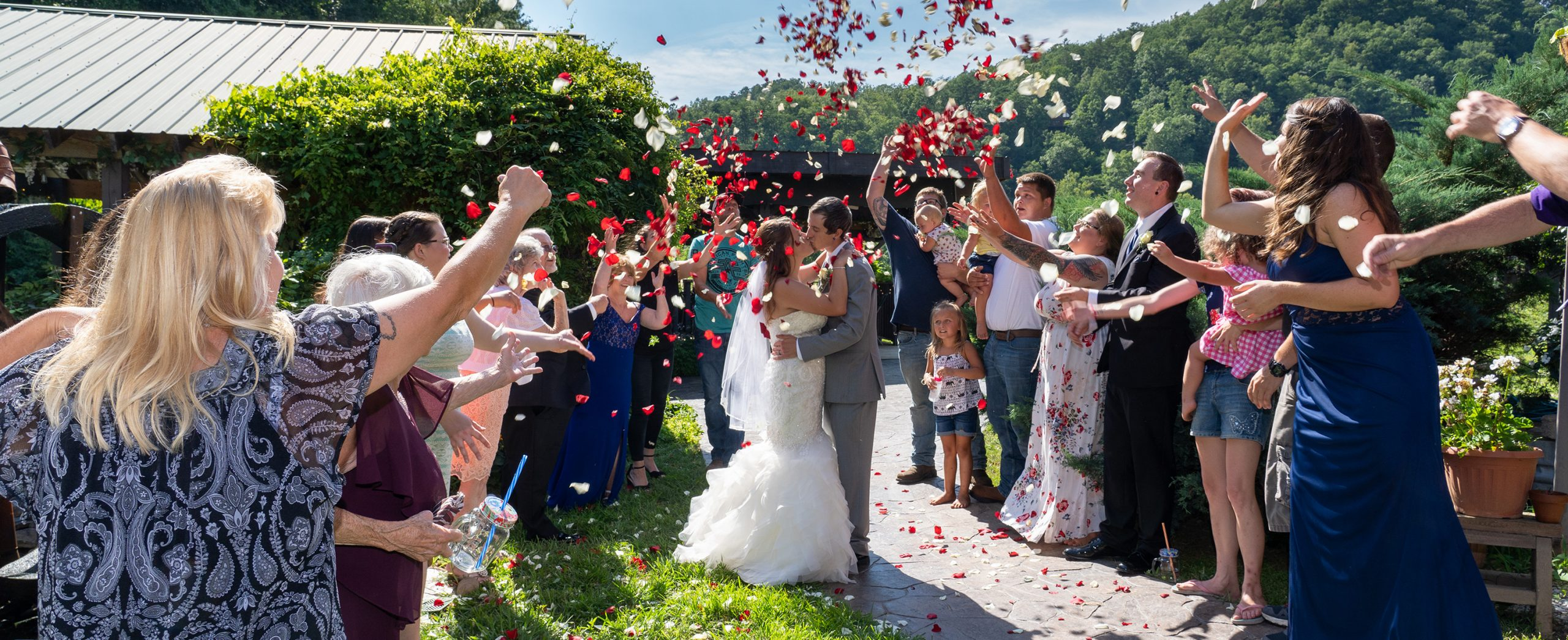 Wedding reception celebration with couple kissing and family tossing rose petals at Honeysuckle Hills in Pigeon Forge