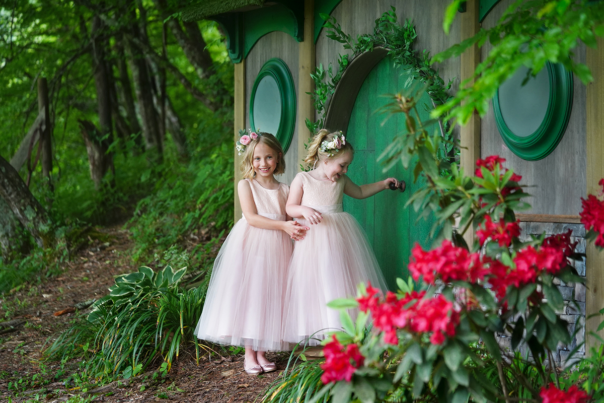 Two flower girls in pink dresses and pink rose flower crowns standing by a green fairy door that looks like a hobbit house in a forest