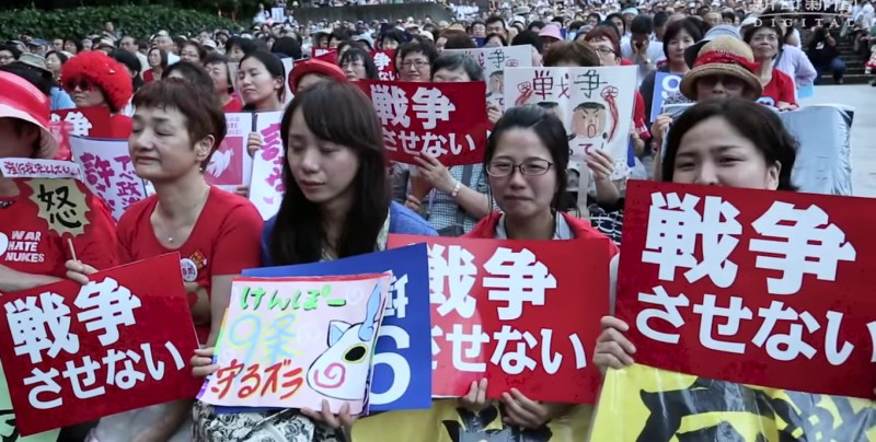 """Protesters in Tokyo hold signs reading """"We will not permit Japan to wage war."""" Screencap from 朝日新聞社 (Asahi Shimbun) official YouTube channel."""