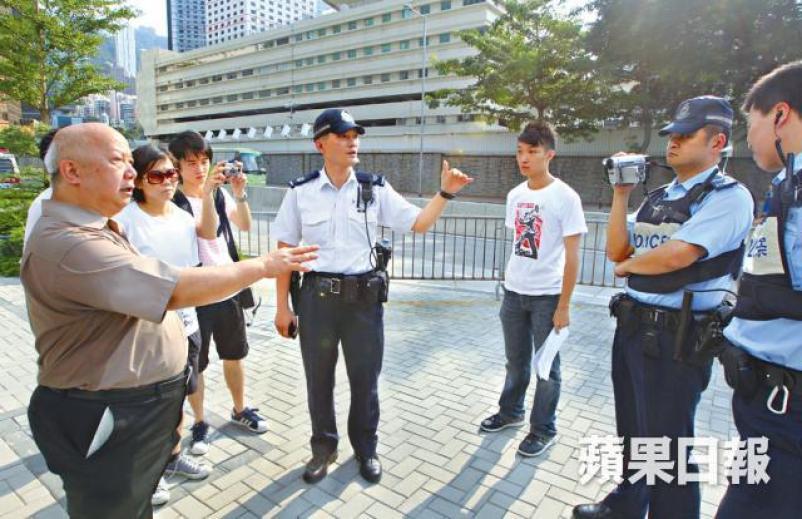 Law Yuk-kai being filmed by police in close range.
