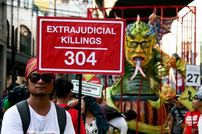 protester holds a poster against the alleged extrajudicial killings