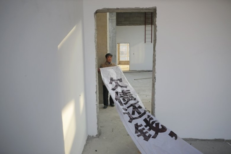 A migrant worker shows a banner inside a building that is under construction as a part of the Zixia Garden development complex in Qianan. Photo: Damir Sagolj, Reuters.