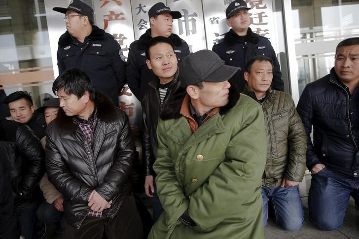 Migrant workers sit in front of policemen as they protest in front of a local government office in Qianan. Photo: Damir Sagolj, Reuters.