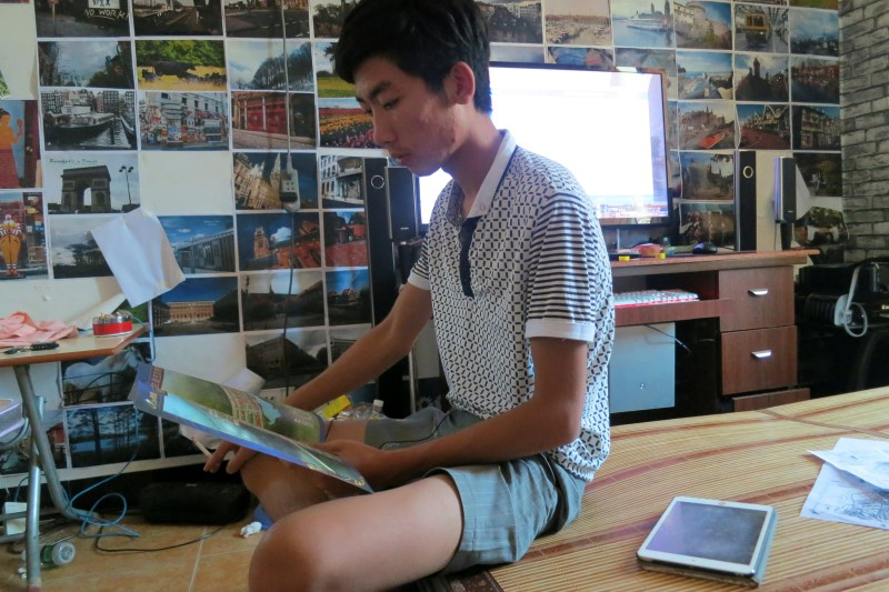Lin Liyi, grandson of arrested village chief Lin Zuluan, looks at a land blueprint in his room in Wukan village in the southern province of Guangdong