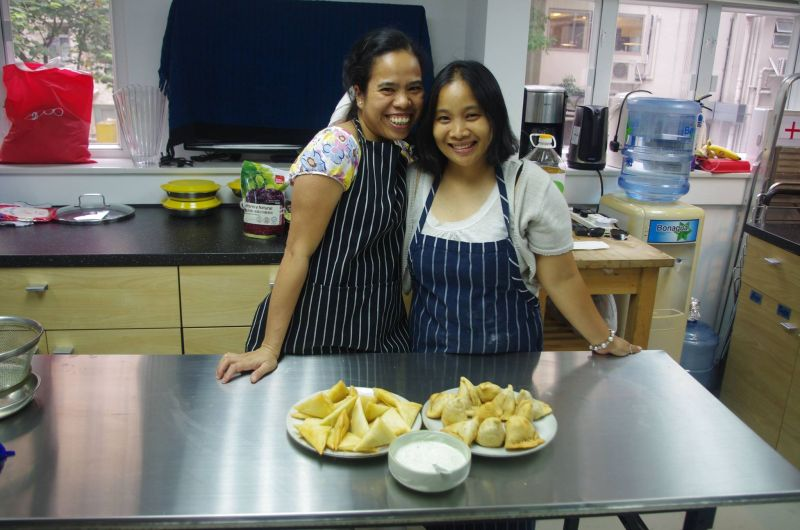 "Domestic helpers Elaine (Left) and ""Melissa"" have learned to make an Indian dish"