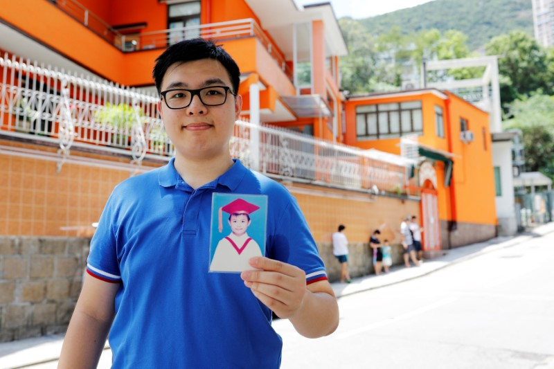Thomas Lui, who was born two month before the handover in 1997, poses with his childhood photo in front of a kindergarten where is him graduated in 2003