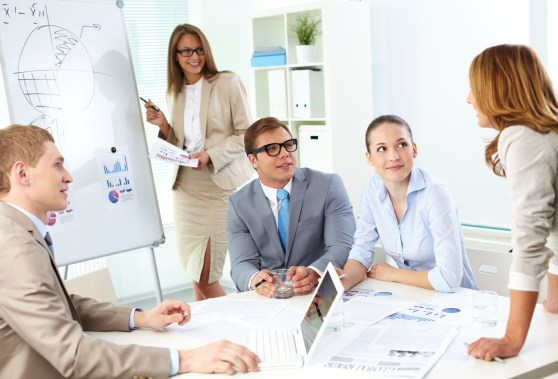 Confident co-workers listening to top manager explanation of her strategy at meeting