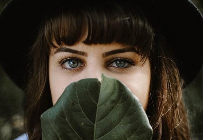 Eine Frau verdeckt ihr Gesicht weil sie Geheimnisse hat