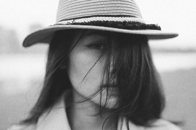 Eine Frau versteckt sich hinter dem Hut, weil sie eine Ablehnung bekommen hat