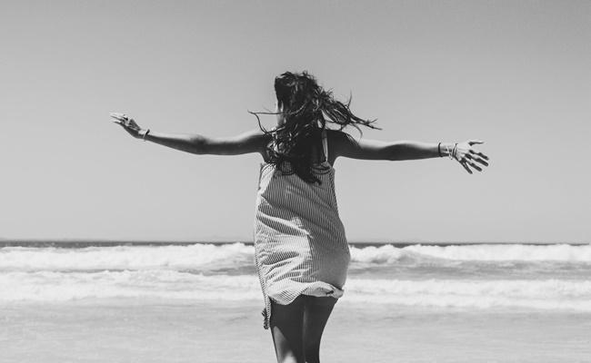 Eine Frau ist steht am Strand und nimmt sich vor ihr Leben zu verändern
