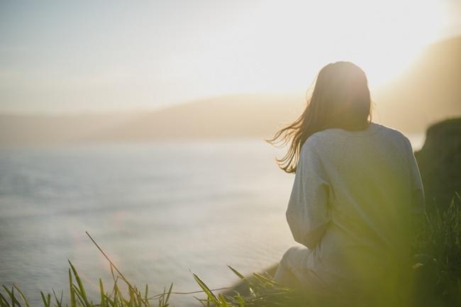 Eine Frau blickt aufs Meer und denkt an ihre Zukunft