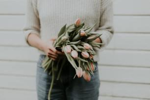 Eine Frau mit Blumen - Symbol für Wertschätzung in Beziehungen
