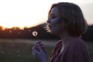 Eine Frau mit Pusteblumen, die ihre Wünsche loslässt