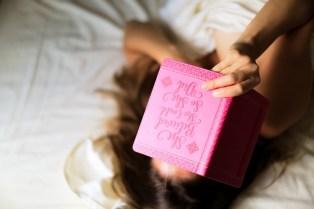 Eine Frau liegt im Bett mit Journaling book
