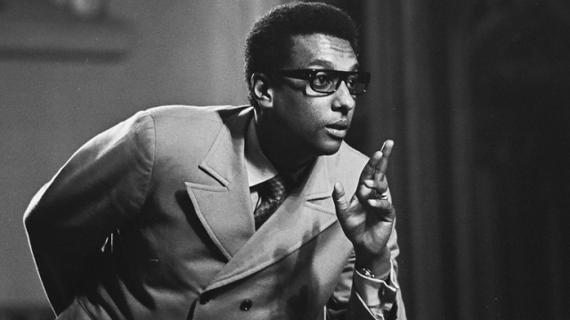 A young Kwame Ture wearing glasses and pointing.