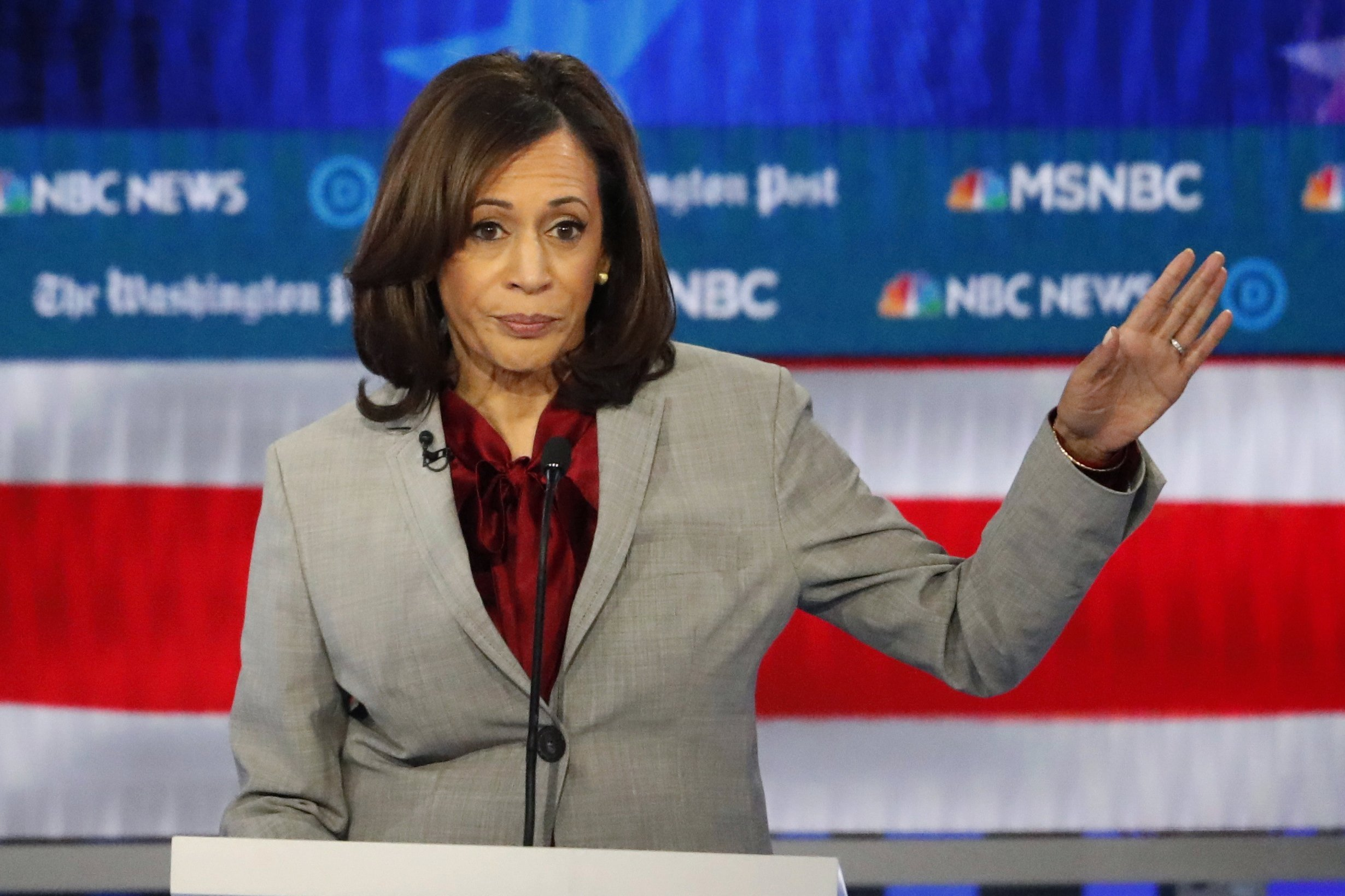Democratic Party vice presidential nominee Kamala Harris waves in front of a red, white, and blue backdrop.