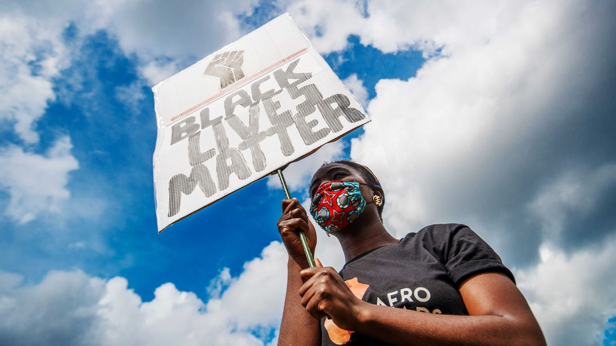 """An African holds a sign that says """"Black Lives Matter"""""""