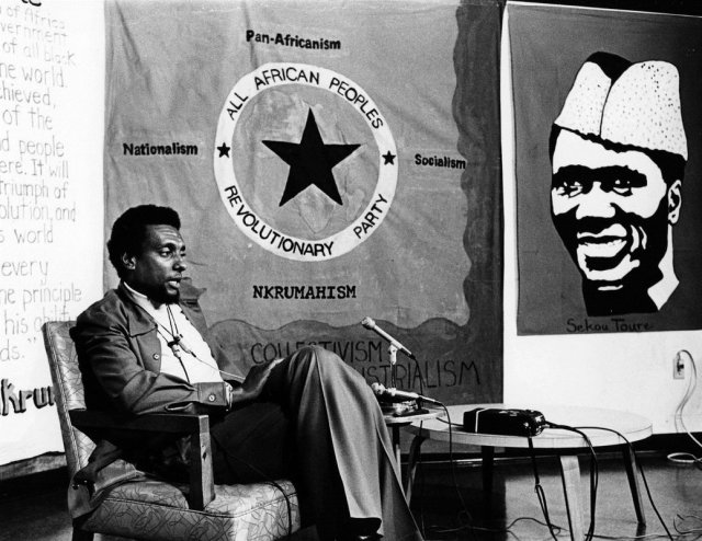 Kwame Ture in front of an AAPRP banner and a picture of Sekou Toure