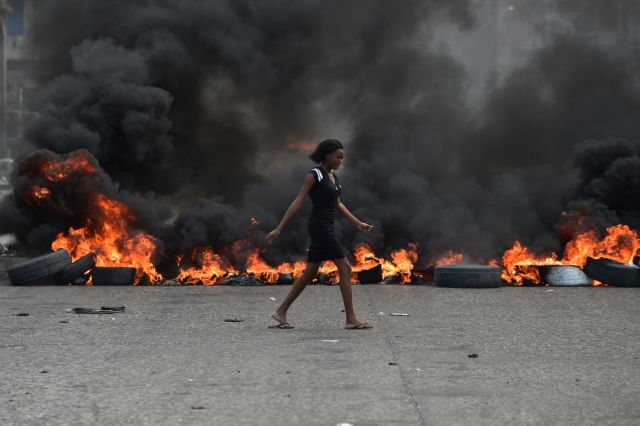 An African walks in front of a flaming tire blockade in the road in Haiti.